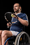Disabled young sportsman sitting in wheelchair and playing tennis Stock Photo