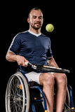 Disabled young sportsman sitting in wheelchair and playing tennis Stock Photography