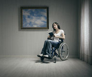 Disabled young woman reading in a wheelchair Stock Photos