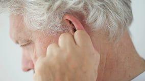 Disagio dell'orecchio in uomo più anziano stock footage