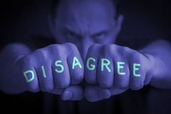 DISAGREE written on an angry man's fists. DISAGREE written on the fingers of an angry man's fists. Blue colored. Message concept image Royalty Free Stock Images