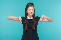 Disagree young woman demonstrate dislike sign. Indoor, studio shot on blue background Stock Images