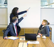 Disagreeing. Two colleagues pointing at a presentation screen, trying to convince a bored looking businesswoman Stock Image