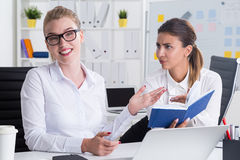 Disagreeing colleagues. Businesswoman in glasses telling her opinion. Her colleague disagrees with her. Concept of mild confrontation at work Royalty Free Stock Photography