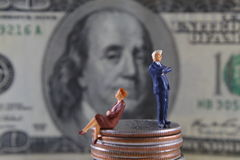 Disagreement. Miniature businessman and businesswoman on stack of quarters Stock Photo