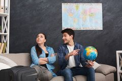 Disagreement in choosing place of vacation. Couple looking for compromise, men pointing on place on globe, sitting with stuff at home, copy space Stock Image