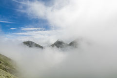 Disappearing mountain peaks. In mist and clouds Stock Photography