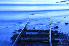 Disappearing Tracks. Train tracks running under water on the coast of Iceland Royalty Free Stock Image