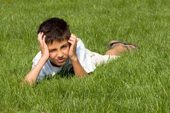 Disappointed. A disappointed teenager is lying in the green grass Stock Images