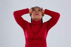 Disappointed African-American girl frantically holding both hands behind head and looking up. stock images