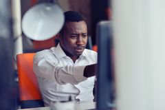 Disappointed African businessman is dazed and confused by a mistake in official documents. Stock Photography