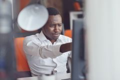 Disappointed African businessman is dazed and confused by a mistake in official documents. Stock Photo