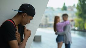 Disappointed African teenager looking female hugging classmate, unrequited love