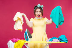 Disappointed angry woman holding clothes and shouting near ironi Stock Photography