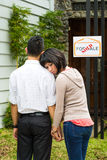 Disappointed asian couple in front of a house Royalty Free Stock Photos