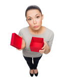 Disappointed asian woman with empty red gift box. Celebration, holidays and happiness concept - disappointed asian woman with empty red gift box Royalty Free Stock Photography