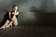 Disappointed ballet dancer sitting in the dark lighted room. Depressed from everything. Upset disappointed exhausted ballet dancer expressing her emotions and Royalty Free Stock Photography