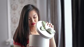 Disappointed beautiful Asian woman wearing red dress opening gift box and getting upset. With her present box. Attractive girl unhappy about bad gift