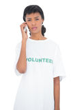 Disappointed black haired volunteer calling someone with her mobile phone Stock Photos