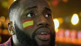 Disappointed black man watching football match, Spanish flag on cheek, loss