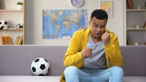 Disappointed black teenager watching football match on TV upset with team losing. Stock footage stock video