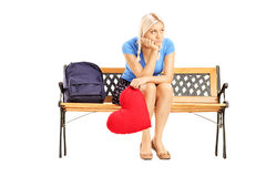 Disappointed blond female sitting on a wooden bench and holding Royalty Free Stock Photo