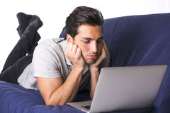 Disappointed or bored young man staring at laptop PC Stock Images