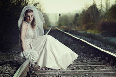 A disappointed bride on a railway Stock Photo