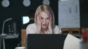 Disappointed business woman throwing document front laptop in dark office. Angry woman touching head in night office. Unhappy girl working late at workplace stock video