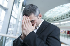 Disappointed businessman with head in hands Royalty Free Stock Photography