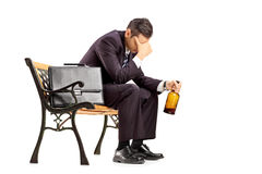 Disappointed businessman sitting on a bench and holding a bottle Royalty Free Stock Images