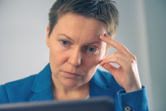 Disappointed businesswoman looking at business results on laptop Stock Images
