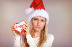Disappointed Christmas woman with a Santa hat holding a gift box Stock Image