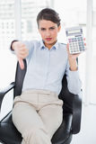 Disappointed classy brown haired businesswoman showing her calculator. In bright office Royalty Free Stock Images