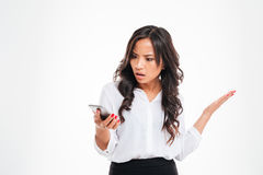 Disappointed confused asian businesswoman using smartphone. Isolated on a white background stock image