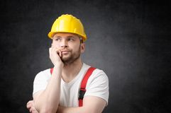 Disappointed construction worker. Unhappy construction worker with yellow hard hat Stock Images
