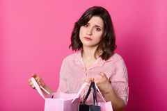 Disappointed dark haired woman, wears rose blouse, holds opened bag. Beautiful brunette looks unhappy, dislikes purchase. Bored. And tired girl buys presents royalty free stock photo