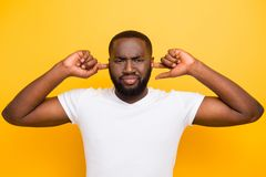 Disappointed depressed attractive handsome manly mulato guy in w. Hite t-shirt, closing ears with fingers, over bright vivid yellow background stock photo