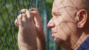 Disappointed and Desperate Man Looking Hopeless Thru a Metallic Fence stock image