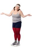 Disappointed fat woman on scale with arms opened Stock Image