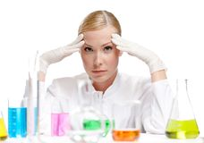 Disappointed female scientist. Is surrounded by medical glassware, isolated on white Royalty Free Stock Photography