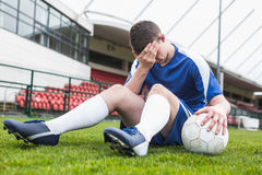 Disappointed football player in blue sitting on pitch after losing Royalty Free Stock Photos
