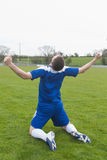 Disappointed football player in blue sitting on pitch after losing Royalty Free Stock Photo