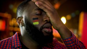 Disappointed german football fan with flag on cheek making facepalm, team losing stock photo