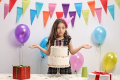 Disappointed girl with a birthday cake. Against a wall with decoration flags and balloons Royalty Free Stock Images