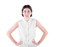 A disappointed girl. A confused girl with hands on hips. An angry female isolated on a white background. Communication problems. stock photo