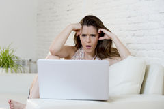 Disappointed girl at home couch using internet for studying with laptop computer Royalty Free Stock Photos