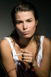 Disappointed girl smoking cigarette Stock Photography