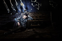 Disappointed guy sits near a chest, holding glass bottle and try. Ing to get out of the trap in a ship, escape the room game concept royalty free stock image