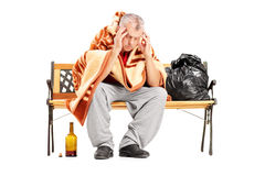 Disappointed homeless mature man sitting on a wooden bench Royalty Free Stock Images
